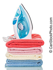 Modern steam iron and stack towels isolated on white.