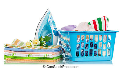 Modern steam iron, a pile of towels and a basket with clothes isolated on white background.