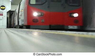 Modern steel subway underground train arriving on one of London metro station in beautiful low angle view