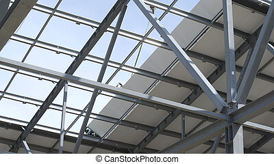 Modern storehouse construction site, structural steel structure of new commercial building against. Construction of modern factory or warehouse. Crane lowers roofing. Man working on roof