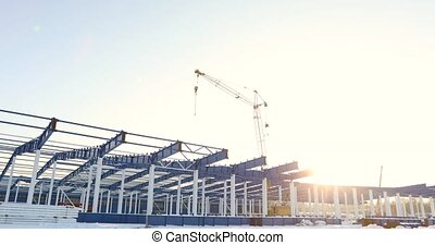 Modern storehouse construction site, the structural steel structure of a new commercial building against a clear blue sky in the background, Construction of a modern factory or warehouse
