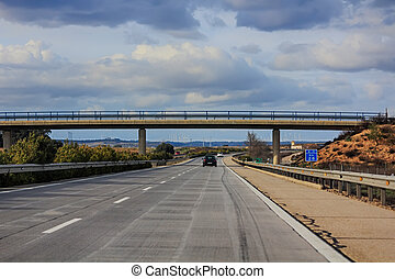 modern straight highway with a bridge in the background