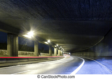 Modern street tunel with one open side and light trails of a moving car