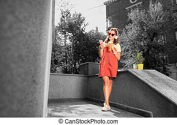 Modern student wearing bright red sunglasses waiting outside for her boyfriend