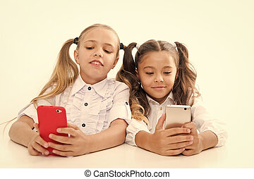 Modern students. Small students using mobile phones in classroom isolated on white. Little students texting message during class. Cute lyceum students diving deep into smartphone lessons.