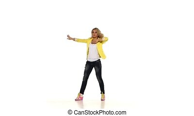 Modern style blond girl in yellow shirt dancing sexy-jazz on white background, slow motion