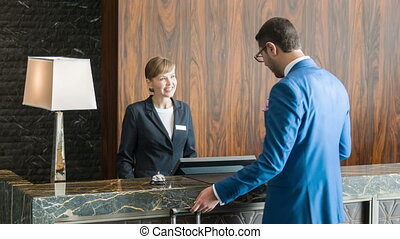 At reception. New visitor dressing lounge suit in eyeglasses having some business trip coming with his valise to receptionist of five-star hotel to register and fill out some forms