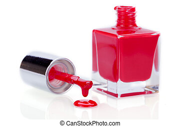 Modern stylish red nail varnish or lacquer displayed as an open glass bottle with the applicator alongside dripping onto a clean white surface with copyspace