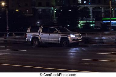 Modern SUV moves along dark city streets.