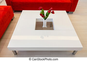 Modern table with red flowers - home interior in white tone