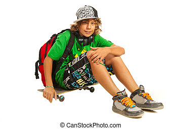 Modern teen schoolboy sitting on skateboard isolated on white background