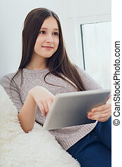 Modern teenage girl using tablet pc
