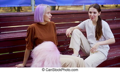 Modern teenage girls with colorful dyed hair sitting on ...