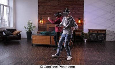 Mixed race friends in futuristic VR glasses carefully moving around domestic room immersed in cyberspace. Advanced teens using augmented-reality goggles and joysticks while playing video game indoors