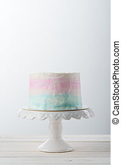 Modern three color cake on a white cake stand, close-up. Light wooden surface, neutral background. Elegant dessert.