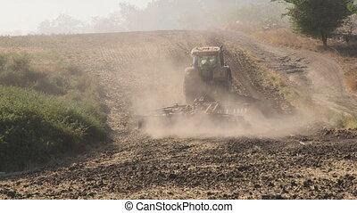 Modern tractor with harrows harrowing field, long shot tilt...
