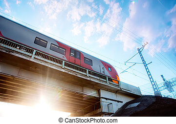 train moves on the bridge at sunset