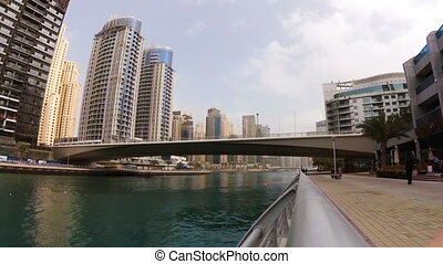 Modern tram passing over the bridge across the river among skyscrapers in Dubai Marina, UAE