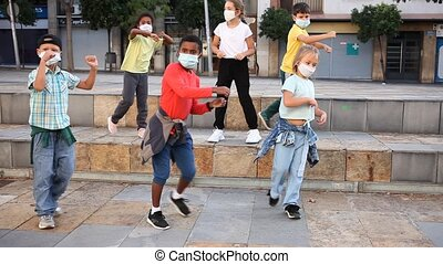 Preteen boys and girls breakdancers in medical masks dancing on city street in summer. Concept of precautions during coronavirus pandemic