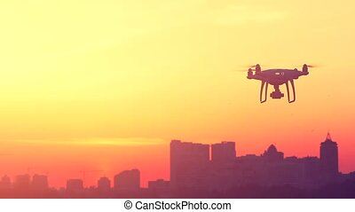 Modern UAV Drone quadcopter with camera flying in dramatic...