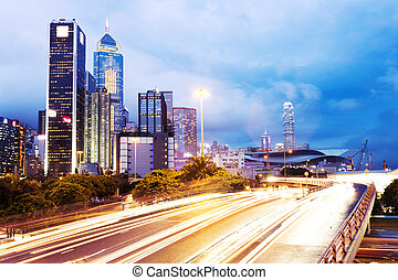modern urban city traffic trails with cityscape background.