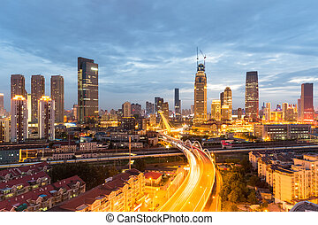 urban scene of tianjin in nightfall, city road and railway with modern buildings, China