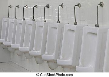 Modern urinal in men bathroom, white ceramic urinals for men in toilet room.