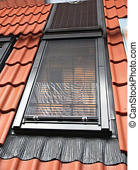 Modern vertical roof window with red tiles