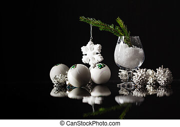 Modern vintage high contrast photo of shiny, bright silver christmas balls decoration lying  on dark black background