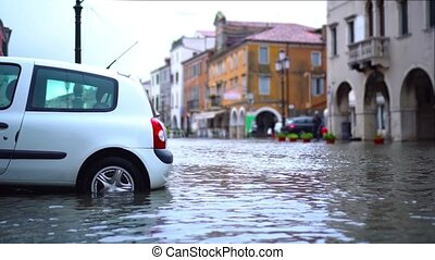 Car wheels stand in high level flood water after canal tides against old buildings in small Italian Chioggia city close view