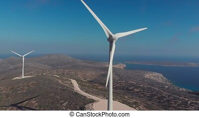 modern white wind generators work on hilly coastline -...