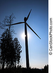 modern wind turbine in front of the evening sun upright