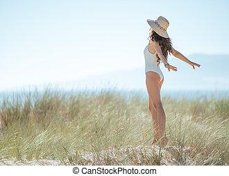 modern woman in white swimsuit on seashore rejoicing