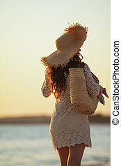 modern woman on ocean coast at sunset walking
