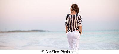 modern woman on seashore at sunset walking