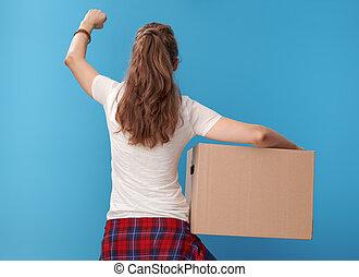 modern woman with cardboard box rejoicing on blue