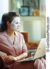 modern woman with facial mask using website on laptop