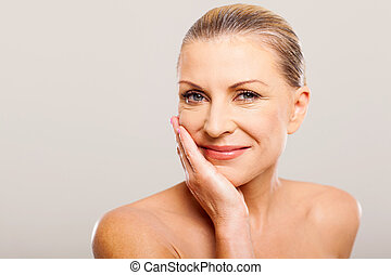 modern woman with hand on her face - modern senior woman...
