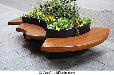 Decorative modern wooden bench with flowers in the street