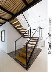Modern wooden staircase in white minimalist interior with...