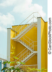Modern yellow and white house with metal zigzag staircase. Courtyard of a building, beautification.