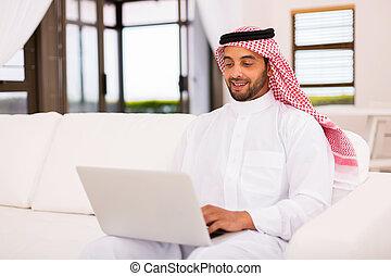 young arabian man using laptop computer - modern young...