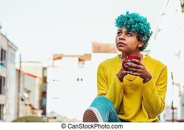 modern young girl with cup of coffee in the city outdoors