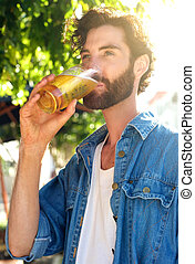 Modern young man drinking beer in summer at outdoor bar