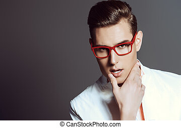Modern young man in white jacket and elegant red glasses....