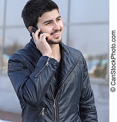young man talking on a mobile phone on the street