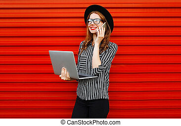 Modern young woman calling on smartphone with laptop on red wall background