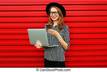 Modern young woman holding laptop looking at phone on red wall background
