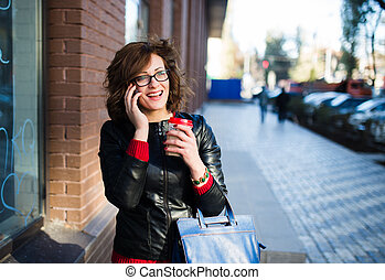 Modern young woman with coffee cup in hand talking on the mobile