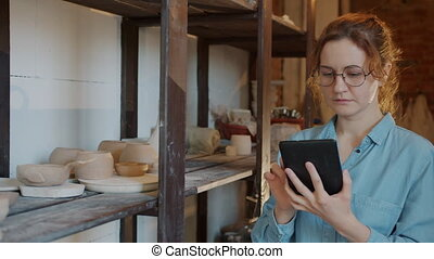 Modern young woman working with tablet in pottery workshop ...